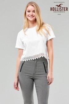 חולצת טי לבנה עם מכפלת תחרהשלHollister