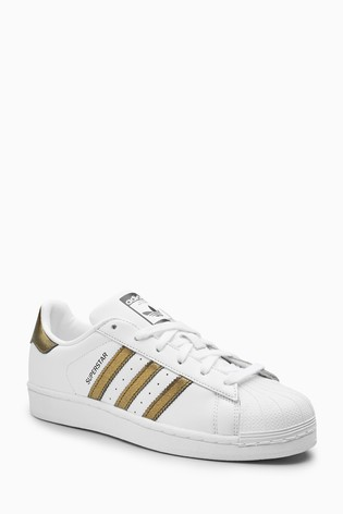 Ejecución Aparador Rebaño  Buy adidas Originals White/Gold Superstar Trainers from the Next ...